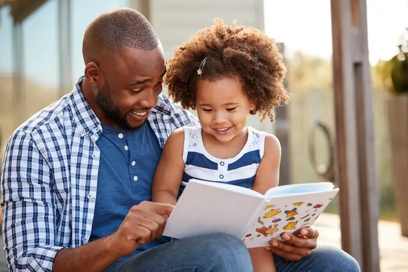 An adult reading to a child
